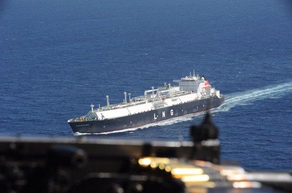 Barco mercante es vigilado por un helicóptero mientras navega por la costa del golfo de Adén.
